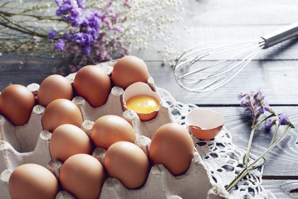 Broken egg among eggs in egg box