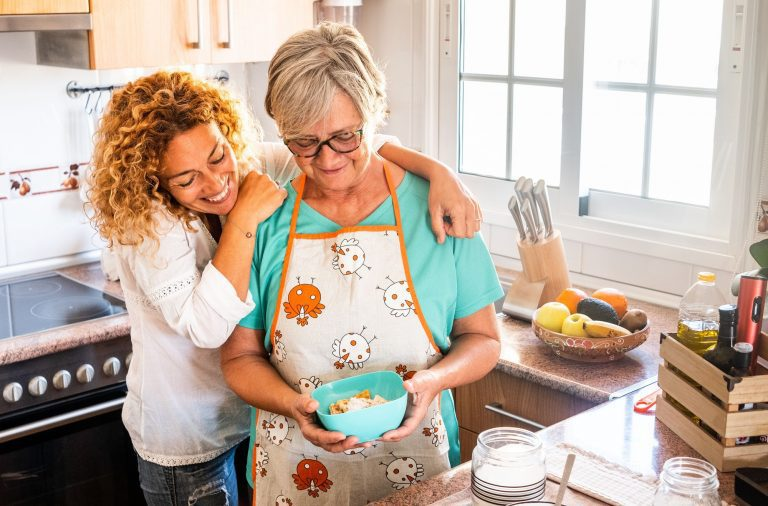 Two women, old and middle age, looking at the homemade baked biscuits smiling in the kitchen